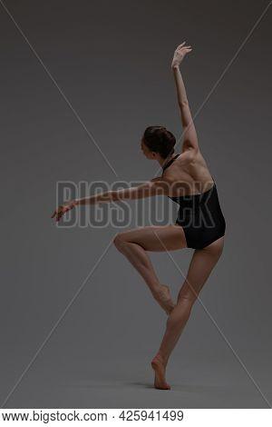 Ballet Dancer In Tutu Posing Against Gray Background