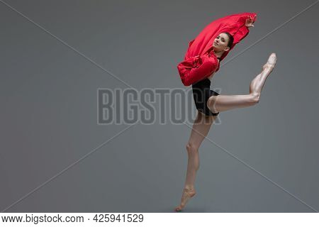 Jumping Ballerina In Tutu Holding Red Silk