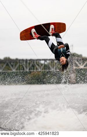 Beautiful Female Wakeboarder Holds Rope And Doing Flips And Jumping Over The Water On Wakeboard