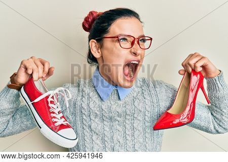 Young caucasian woman choosing high heel shoes and sneakers angry and mad screaming frustrated and furious, shouting with anger. rage and aggressive concept.