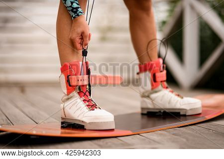 Close-up View On Athletic Female Legs Fixed In Boots Of Wakeboarding Board