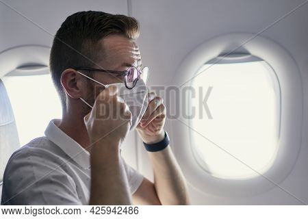 Passenger Wearing Protective Face Mask In Airplane. Themes Traveling In New Normal And Personal Prot