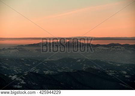 Magnificent View Of Mountain Peak Against Background Of Bright Orange Sky With Clouds On Top