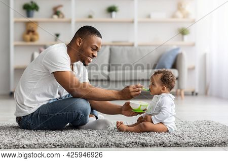 Paternity Leave. Happy Black Dad Feeding Infant Baby From Spoon At Home