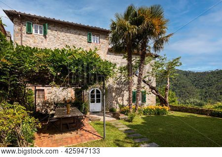 Typical Italian farmhouse of Tuscany. Exterior with large garden stone walls and palm trees