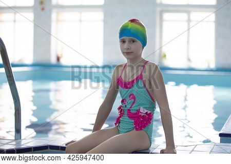 Girls In A Swimsuit And A Swimming Cap In The Sports Pool.