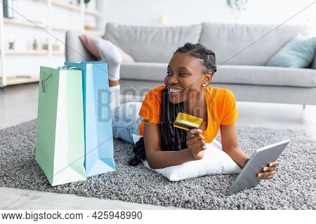 Shopaholism And E-commerce. Black Lady With Credit Card Shopping Online Via Laptop, Lying On Floor W