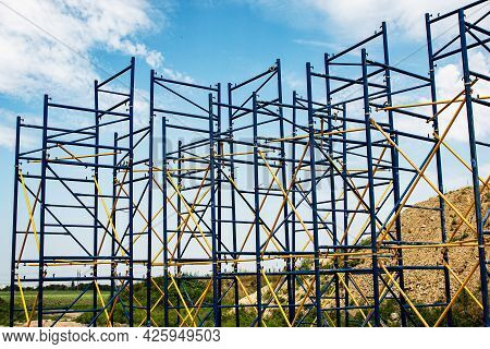 Construction Site With Scaffolding Tower And Building. Scaffolding For A Construction Factory.