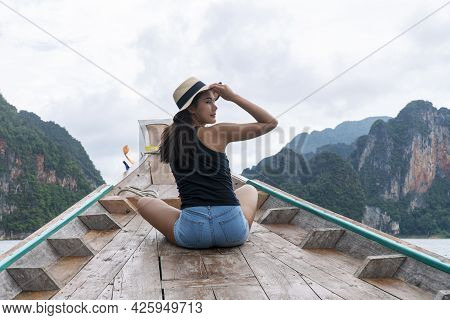 Adventure Lifestyle Vacationer Relax Concept. Traveler Young Woman Wear Hat Sitting On Long Tail Boa