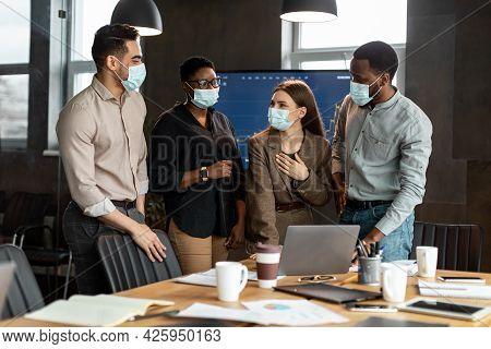 Colleagues In Masks Having Meeting In Boardroom, Talking