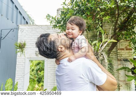 Cheerful Father Holding And Kiss Baby Daughter In His Hand While Relax Time At Home. Mixed Race Litt