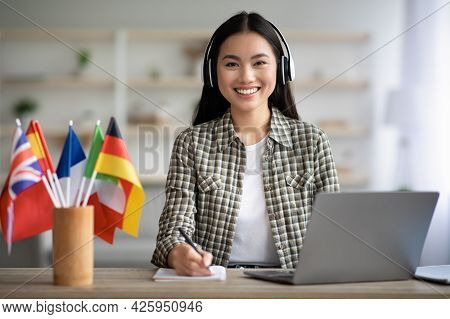 Smiling Asian Lady Using Laptop And Headset, Learning Foreign Language