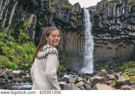 Portrait of woman on Iceland. Hiker enjoying Svartifoss waterfall. Female is visiting famous tourist attraction of Iceland. Natural landmark on vacation in Skaftafell. Icelandic nature landscape.
