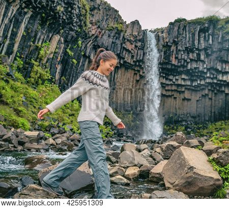 Iceland. Hiker enjoying majestic Svartifoss waterfall. Female is visiting famous tourist attraction of Iceland. Spectacular natural landmark on vacation in Skaftafell. Icelandic nature landscape.