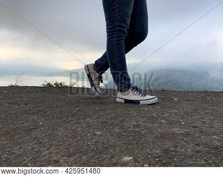 Legs Of A Person. Feet Walking On Top Foggy Mountain Nature View Background. Keep Walking Forward. H