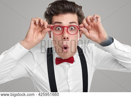 Amazed Male Nerd In Glasses And Stylish Clothes Looking At Camera In Astonishment On Gray Background