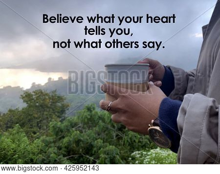 Nspirational Quote - Believe What Your Heart Tells You, Not What Others Say. With Hand Of A Person H