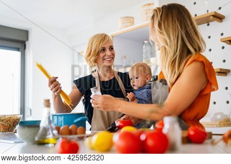 Lesbian Mothers With Adopted Child. Happy Homosexual Family Playing With Her Daughter