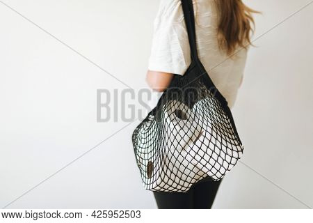 Woman with tissue papers in a net bag