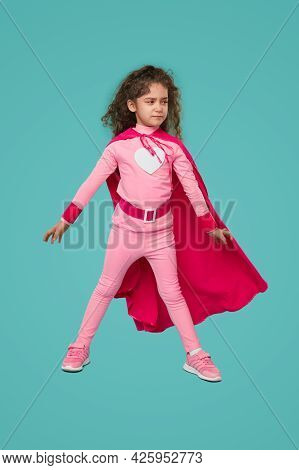 Determined Girl In Pink Superhero Costume Looking Away With Serious Face Before Saving World Against