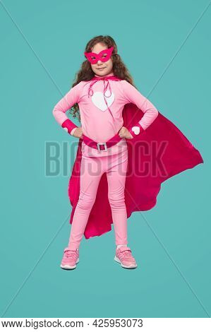 Full Body Of Confident Little Girl In Pink Masquerade Mask And Superhero Costume Looking At Camera,
