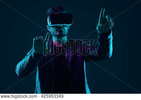 Contemporary Young Bearded Guy In Virtual Reality Goggles Pressing Invisible Button While Exploring