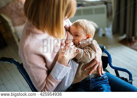 Young Mother With Disability In Wheelchair Breast Feeding Her Child At Home