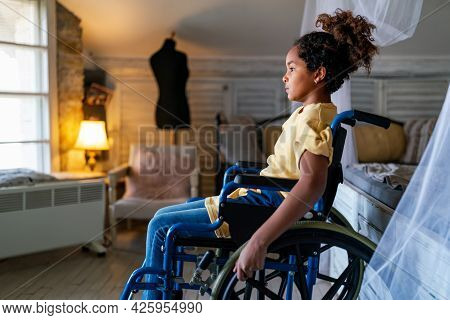 Black Little Girl With Disability In Wheelchair At Home