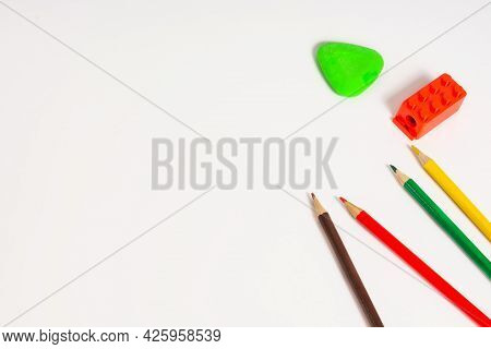White Background With Colored Pencils And Erasers. School Supplies And Office Supplies Are On A Whit