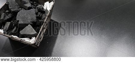 Black Charcoal On Black Textured Floor.