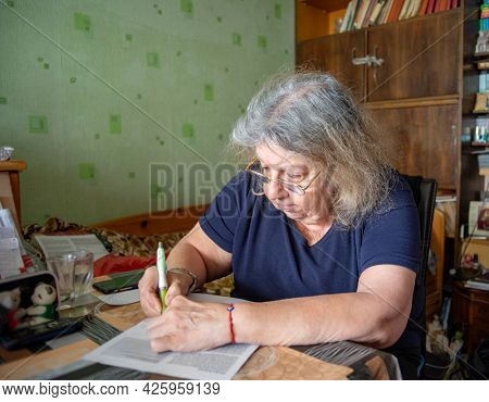 Elderly jewish pensioner in her seventies is signing documents at home.