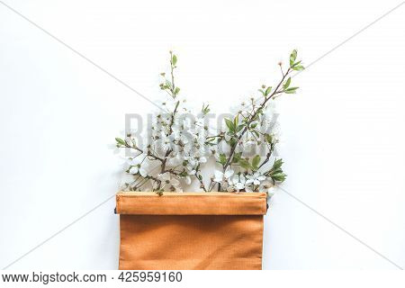 Sprig Of Cherry Blossom In A Orange Canvas Bag On A White Background. Eco Concept, Copy Place, Flat