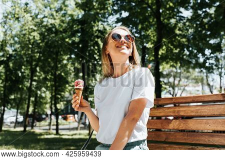 Joyful Young Woman Relaxing On A Park Bench Looking Up Enjoying The Sun And Summer Weather. Cute Smi