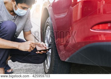Asian Man Car Inspection Measure Quantity Inflated Rubber Tires Car.close Up Hand Holding Smartphone