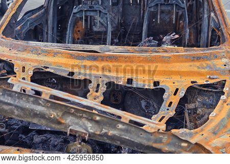 Burnt-out Rusty Cars On A City Street, Vandalism. Setting Fire To Cars By Vandals And Damage To Prop
