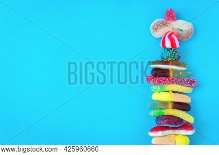 Set Of Multi-colored Marmalades On A Stick On A Bright Blue Background