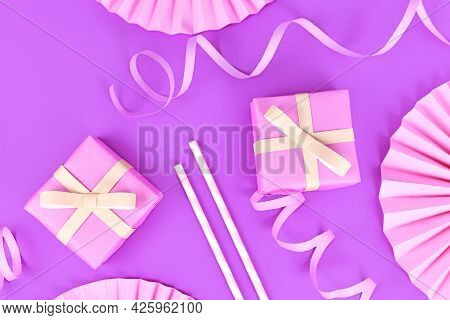 Violet Party Flat Lay With Pink Gift Boxes, Paper Streamers, Drinking Straws And Paper Rosettes
