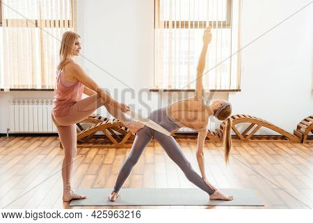 Yoga Teacher Or Pilates Instructor Helping Young Woman To Stretch Muscles With Rope