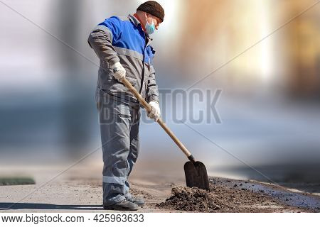 A Laborer In A Medical Mask And Work Clothes Stands With A Shovel On A Blurry Background. Physical L