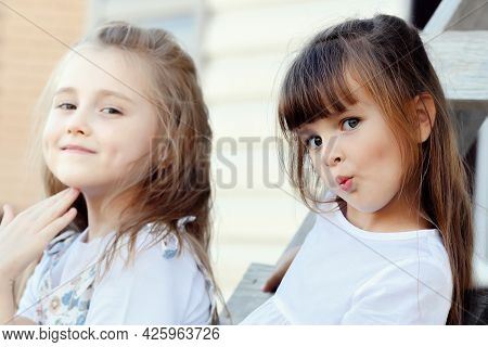 Two Beautiful Girls Girlfriends Sit On A Summer Day On A Wooden Staircase And Look Into The Camera A