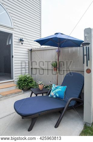 Condo Outdoor Patio with Blue Chaise Lounge and Umbrella, Vertical