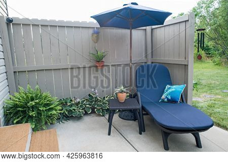 Condo Outdoor Patio with Blue Chaise Lounge and Umbrella, Horizontal