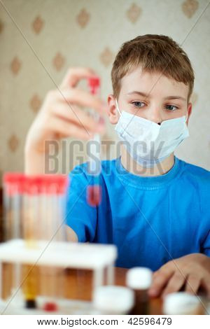 Boy in mask-respirator sits at table with chemical reagents and looks at a test tube, which he holds in his hand