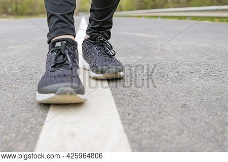 Morning Run. Running Feet While Running, Runner In Black Sneakers Runs On The Asphalt.