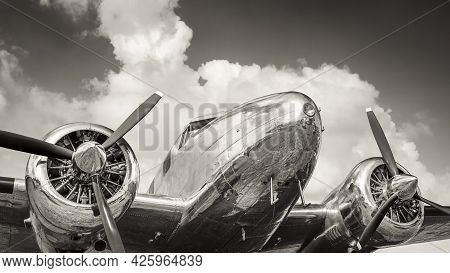 Historical Propeller Aircraft Against A Cloudy Sky