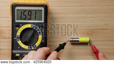 Testing AA battery cell with digital multimeter tool, voltage check showing good value, battery is still new and full charge