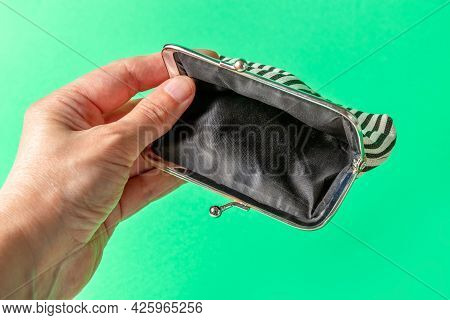 Open Empty Wallet In Hand On A Green Background. Poverty Concept. Below The Poverty Line.
