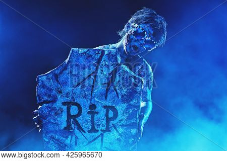 Horrible Halloween party. Scary zombie boy teenager in party sunglasses peeps out from behind the headstone in the cemetery. Event invitation.