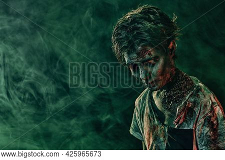 Halloween concept. Portrait of a scary zombie boy teenager in smoke. Horror movie. Copy space.