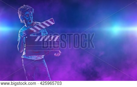 Halloween zombie boy teenager holds a clapperboard. Halloween and Horror movie. Copy space.